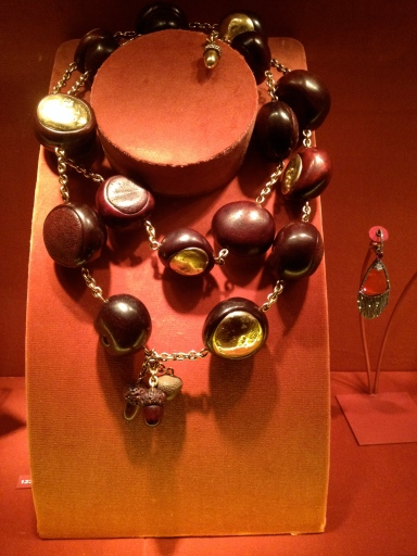 This is called the Chestnut and Acorn necklace, made in 2006. It's made out of wood and gold. On view at MET Museum.